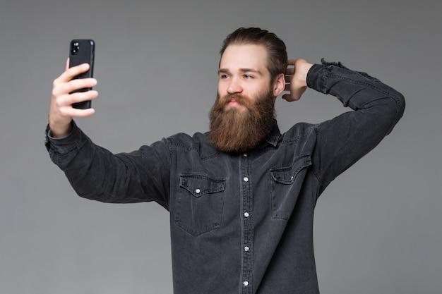 Feliz sonriente hombre inconformista con barba larga tomando selfie con las manos en la barba de pie en el espacio gris
