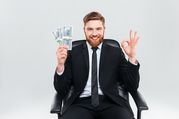 Feliz sonriente hombre de negocios en traje negro con dinero en una mano, mostrando el signo de ok y sentado en el sillón. fondo gris aislado