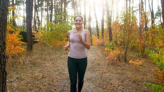 Feliz sonriente joven corriendo y haciendo fitness en el bosque de otoño.