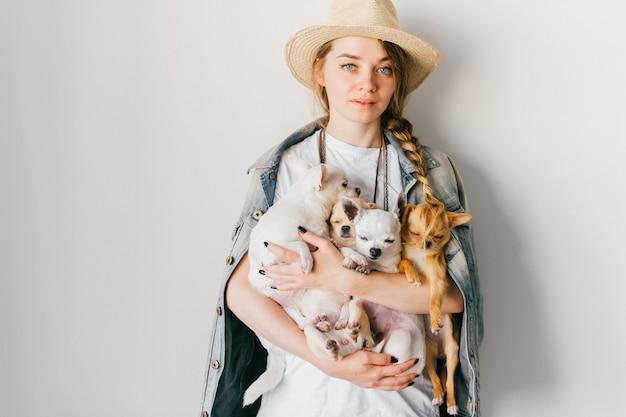 Feliz sonriente joven elegante con cuatro cachorros de chihuahua encantadora en sus manos sobre la pared blanca.