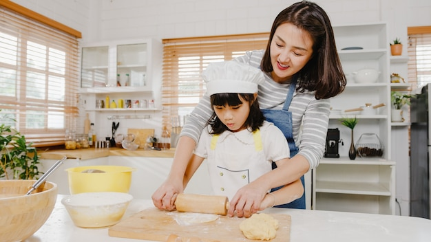 Feliz sonriente joven familia asiática japonesa con niños en edad preescolar se divierten cocinando pasteles para hornear