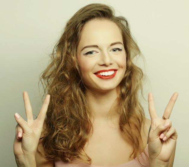Feliz sonriente joven hermosa mostrando los pulgares para arriba gesto
