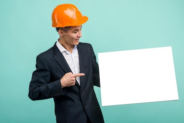 Feliz sonriente joven ingeniero asiático hombre señala con el dedo letrero en blanco