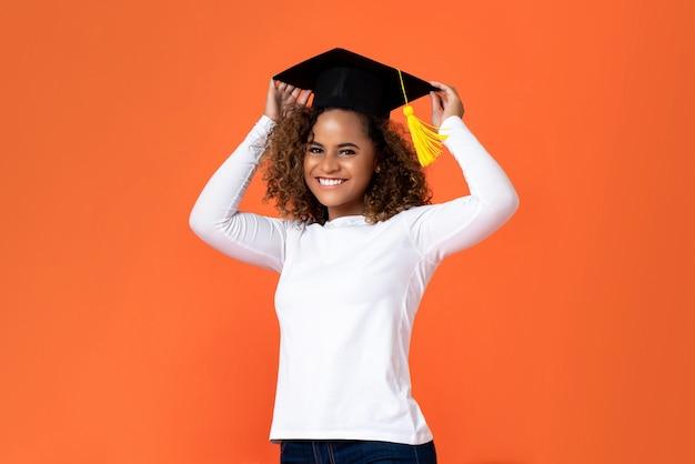 Feliz sonriente joven mujer afroamericana con gorro de graduación