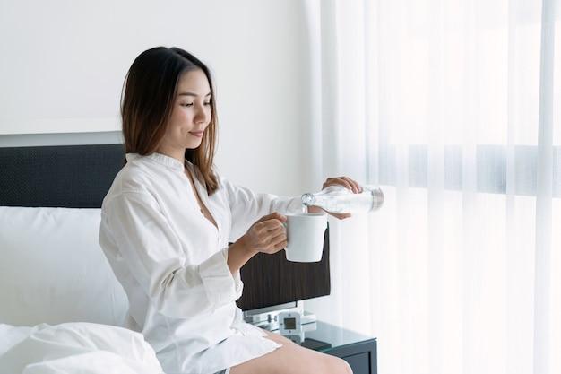 Feliz sonriente joven mujer asiática bebiendo agua después de despertarse por la mañana.