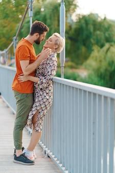 Feliz sonriente joven pareja abrazándose y besándose en el puente