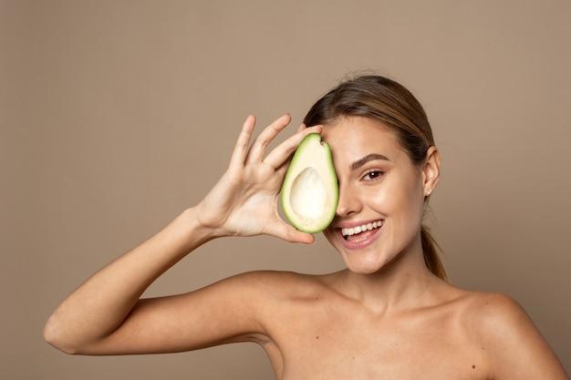 Feliz sonriente joven sosteniendo la mitad de aguacate sobre un fondo beige. concepto de belleza natural.