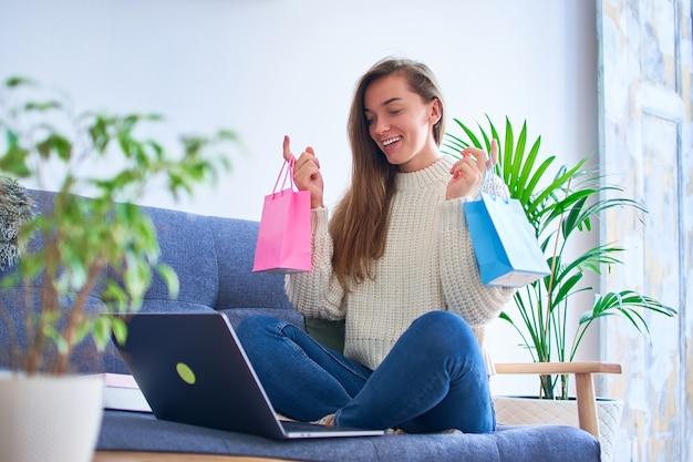 Feliz sonriente linda contenta satisfecha alegre mujer adicta a las compras recibió regalos en línea y sostiene bolsas de papel de colores
