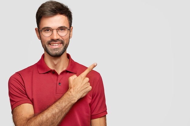 Feliz sonriente macho europeo con cerdas, puntos con el dedo índice a un lado, lo invita a cenar en el restaurante situado cerca, vestido con una camiseta roja informal, gafas aisladas en una pared blanca