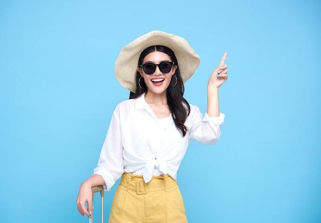 Feliz sonriente mujer asiática vestida con ropa de verano y con sombrero con equipaje disfrutando de sus vacaciones de verano y señalando con el dedo un espacio de copia en la pared azul brillante.