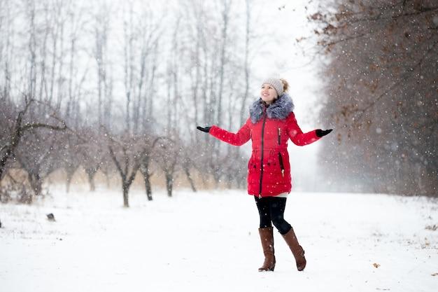 Feliz sonriente mujer en chaqueta de invierno rojo disfruta de la nieve, al aire libre, en el parque