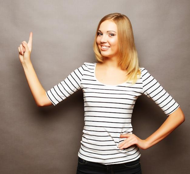 Feliz sonriente mujer joven hermosa que muestra copyspace, im visual