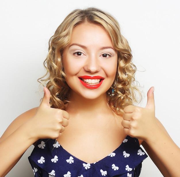 Feliz sonriente mujer joven hermosa que muestra los pulgares arriba gesto