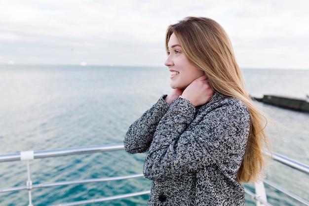 Feliz sonriente mujer de pelo largo con grandes ojos azules en camisa roja y abrigo gris camina cerca del mar