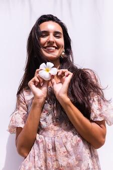 Feliz sonriente mujer de pelo largo en vestido se encuentra en la pared blanca