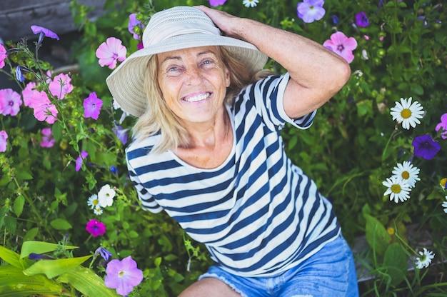 Feliz sonriente mujer senior posando en el jardín de verano con flores en sombrero de paja.