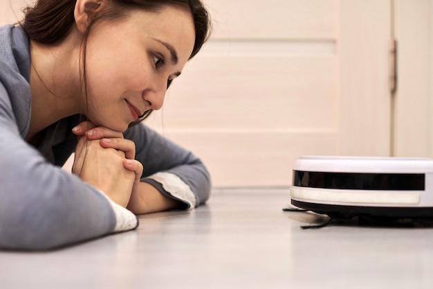 Feliz sonriente mujer tendida en el suelo y mirando la aspiradora robótica. conociendo a un nuevo robot amigo y feliz con el dispositivo inteligente