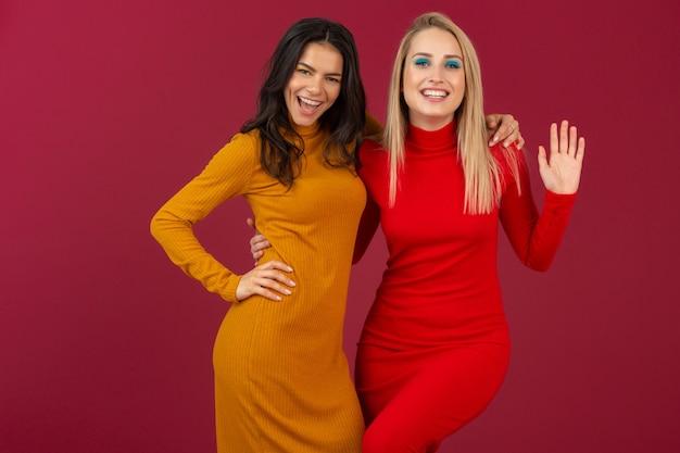 Feliz sonriente a mujeres muy elegantes en amarillo y rojo otoño invierno vestido de punto de moda posando aislado en la pared roja