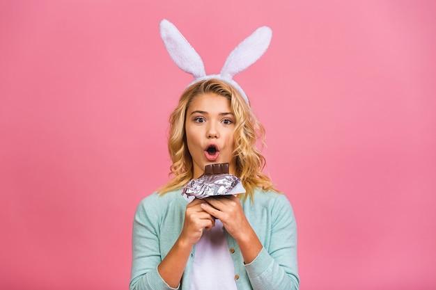 Feliz sonriente niña adolescente o niño mordiendo sabroso chocolate con espacio de copia vacío