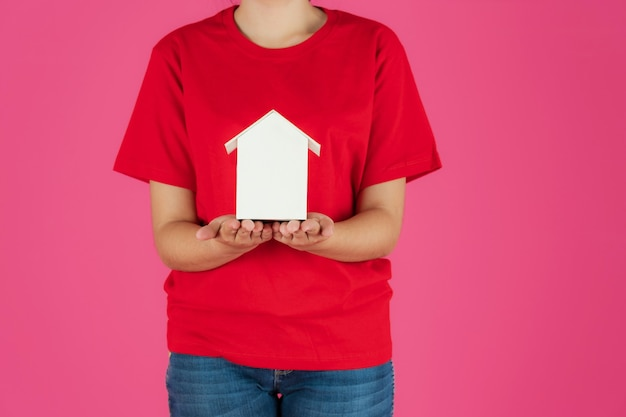 Feliz sonriente niña asiática de pie con casa de papel sobre fondo rosa