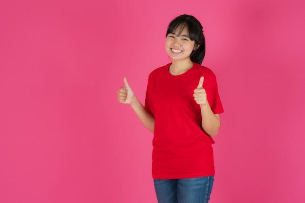 Feliz sonriente niña asiática de pie sobre fondo rosa
