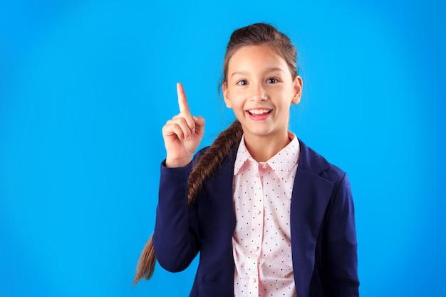 Feliz sonriente niña estudiante de primaria en uniforme apuntando su dedo hacia arriba
