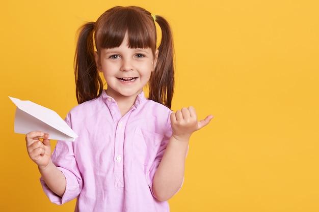 Feliz sonriente niña vistiendo ropa casual con avión de papel en la mano
