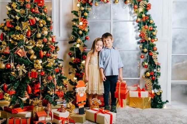 Feliz sonriente niños abrazos en estudio con árbol de navidad decorado y cajas de regalo