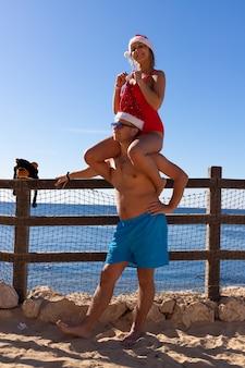 Feliz sonriente pareja de enamorados celebran la navidad y el año nuevo en el mar rojo.