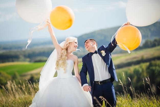 Feliz, sonriente recién casados con globos de helio se divierten después de la ceremonia de la boda