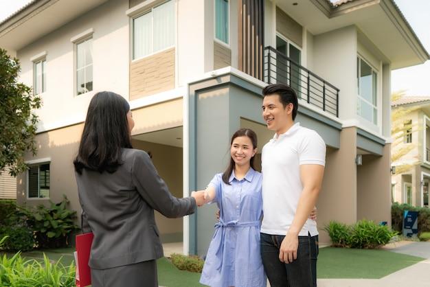 Feliz sonrisa asiática joven pareja apretón de manos con agente inmobiliario o agente de bienes raíces en frente de su casa después de firmar un contrato