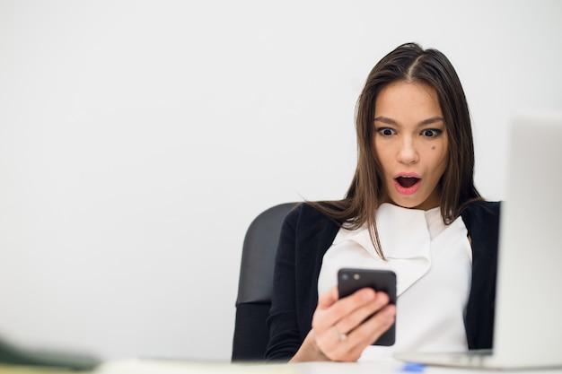 Feliz sorprendente mujer mirando en el teléfono móvil y leyendo el mensaje con la boca abierta