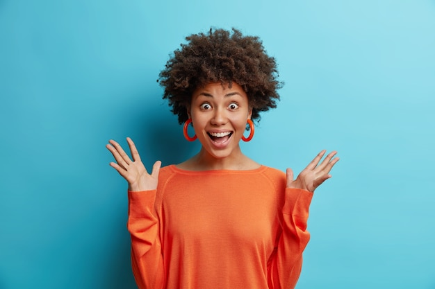 Feliz sorprendida atractiva mujer afroamericana levanta las manos reacciona ante impresionante relevación inesperada