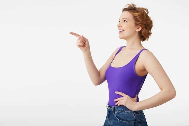 Feliz sorprendida joven atractiva de pelo corto, vestida con una camiseta morada, vio algo divertido y le señala con el dedo, mire el espacio de la copia aislado sobre la pared blanca.
