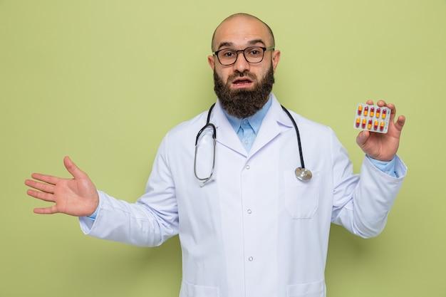 Feliz y sorprendido médico hombre barbudo en bata blanca con estetoscopio alrededor del cuello con gafas sosteniendo blister con pastillas sonriendo alegremente con el brazo levantado