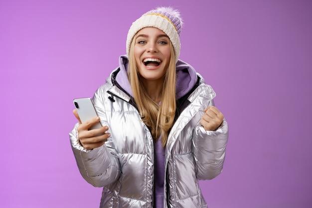 Feliz suerte encantadora rubia triunfadora ganadora de lotería primer premio recibir mensaje de buenas noticias smartphone aprieta puños celebrando el éxito gritando sí logrado, de pie fondo púrpura.
