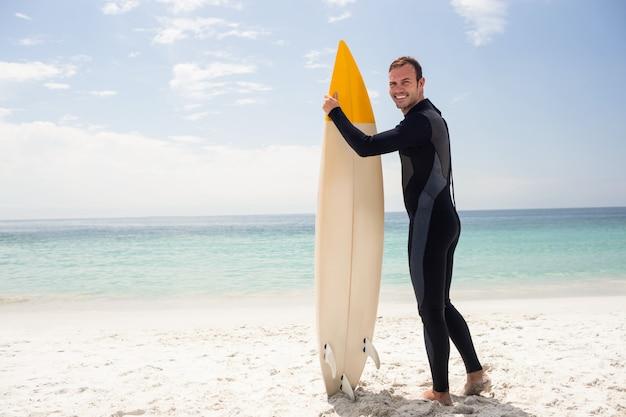 Feliz surfista sosteniendo una tabla de surf en la playa