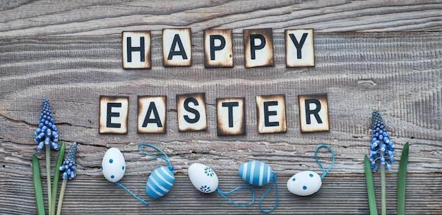 Feliz texto de pascua en madera rústica con flores de jacinto azul y huevos de pascua