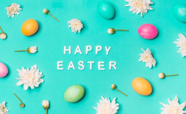 Feliz título de pascua entre conjunto de huevos brillantes y capullos de flores