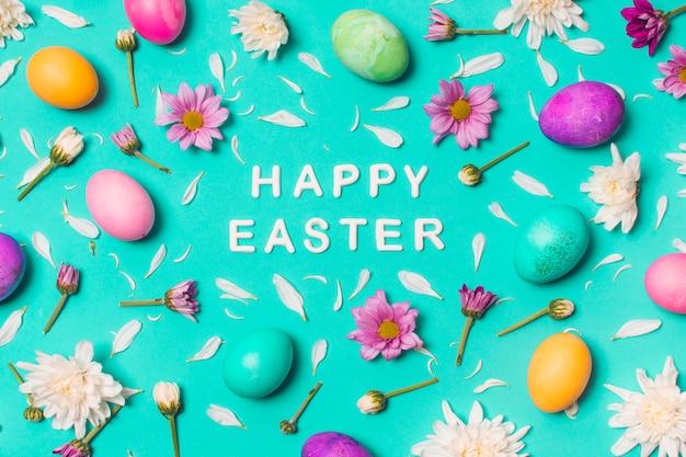 Feliz título de pascua entre huevos brillantes y capullos de flores.