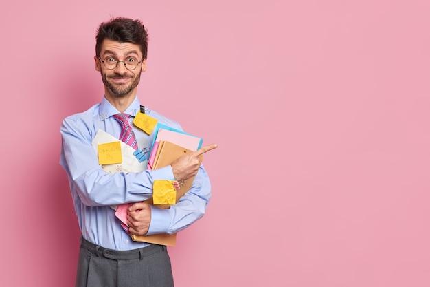 Feliz trabajador de oficina positivo sin afeitar demuestra los resultados de su trabajo de investigación pegados con pegatinas sostiene carpetas con documentos indica a un lado en el espacio en blanco