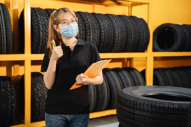 Feliz trabajadora asiática usa una máscara para evitar la propagación del virus corona o covid-19 comprobando el stock de neumáticos de automóvil en el almacén