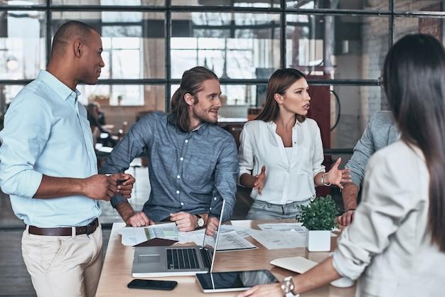 Feliz de trabajar juntos. grupo de jóvenes empresarios que se comunican mientras trabaja en la oficina
