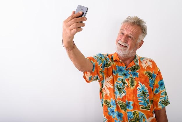 Feliz turista barbudo senior hombre sonriendo mientras toma una foto selfie con teléfono móvil en blanco