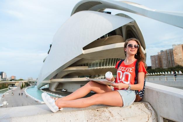 Feliz turista femenina con un mapa en la ciudad de las artes y las ciencias de valencia.