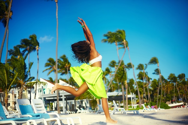 Feliz urbano moderno joven elegante mujer modelo mujer en tela moderna brillante en falda colorida verde al aire libre en la playa de verano saltando detrás del cielo azul