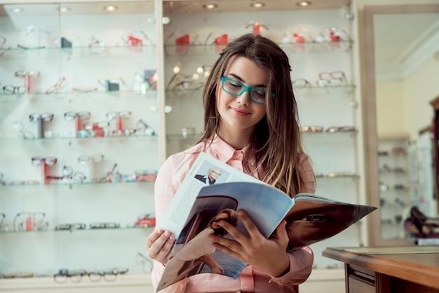 Feliz de ver las palabras claramente sin desenfoque. retrato interior de mujer europea atractiva satisfecha sentada en la tienda de óptica mientras lee la revista con gafas, esperando a que gire para comprobar la vista