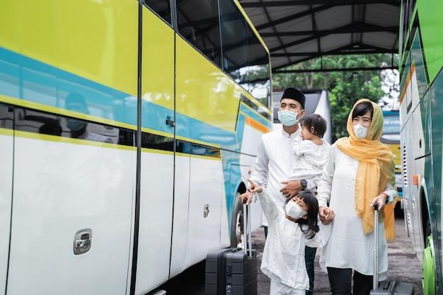 Feliz viaje de vacaciones musulmanas asiáticas en autobús junto con la familia con máscara para prevenir la propagación del virus