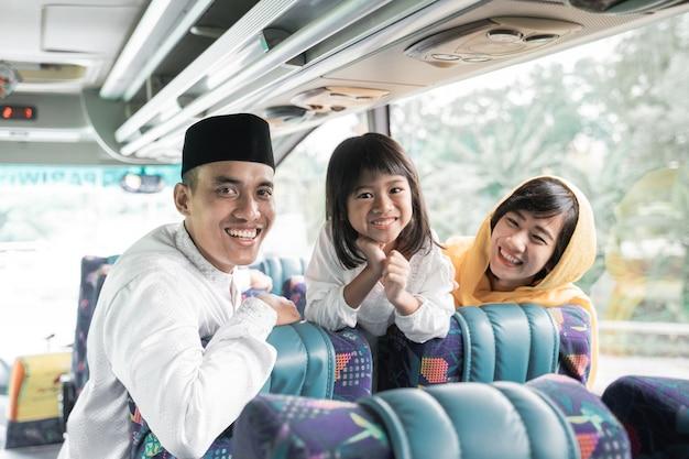 Feliz viaje de vacaciones musulmanas asiáticas en autobús junto con la familia