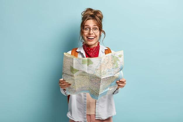 Feliz viajera sostiene el mapa, verifica la ruta del destino, viaja por europa durante las vacaciones, lleva mochila, usa gafas redondas